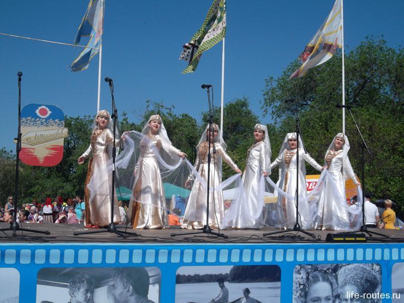 А на сцене гостей развлекают фольклорные коллективы