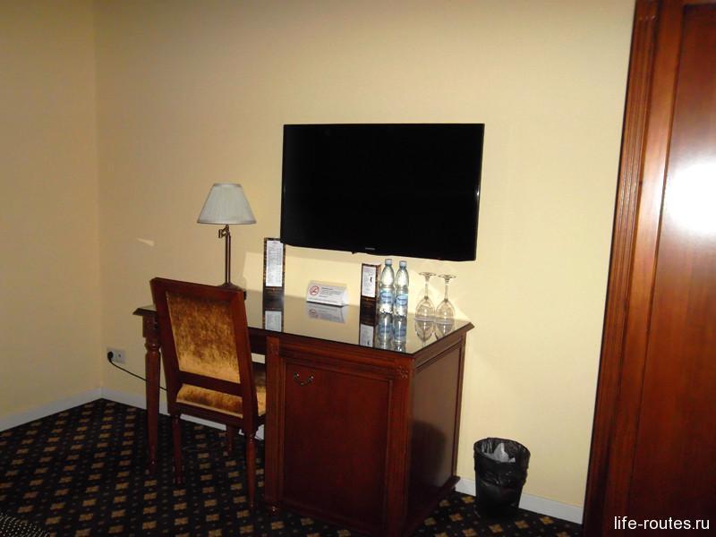 Столик, телевизор и приятный бонус в виде двух бутылок воды для гостей