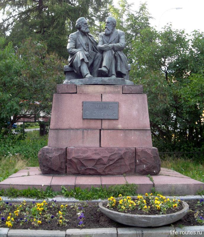 Недалеко от площади в тени деревьев притаились К. Маркс и Ф. Энгельс