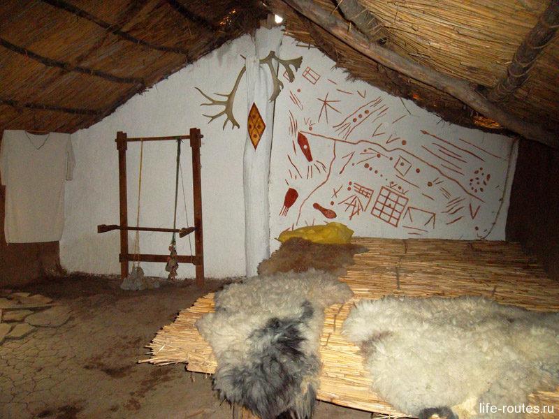 Кровать из камыша накрытая шкурами для всей семьи, на стене рисунки
